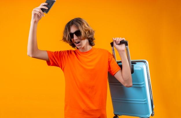 Junger hübscher kerl im orangefarbenen t-shirt, das schwarze sonnenbrillen hält, die flugtickets und reisekoffer halten, die überrascht und glücklich stehen über gelbem hintergrund stehen
