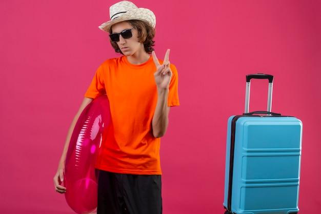 Junger hübscher kerl im orangefarbenen t-shirt, der schwarze sonnenbrille hält, die aufblasbaren ring hält, der mit reisekoffer steht, der zuversichtlich zeigt, siegeszeichen zu zeigen
