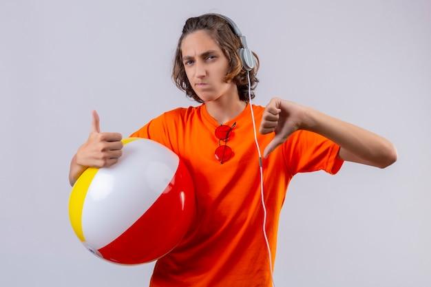 Junger hübscher kerl im orangefarbenen t-shirt mit kopfhörern, die aufblasbaren ball halten, missfiel, daumen oben und unten stehend zeigend