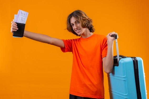 Junger hübscher kerl im orangefarbenen t-shirt stehend mit reisekoffer, der flugtickets hält, die fröhlich positiv und glücklich über gelbem hintergrund lächeln