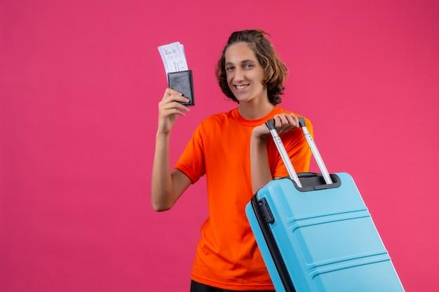 Junger hübscher kerl im orangefarbenen t-shirt stehend mit reisekoffer, der flugtickets hält, die fröhlich über rosa hintergrund lächeln
