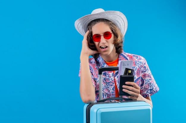 Junger hübscher kerl im sommerhut, der rote sonnenbrille mit reisekoffer hält, der flugtickets hält, die mit hand auf kopf für fehler verwirrt verwechseln, erinnern sie sich fehler, der über blauem hintergrund steht