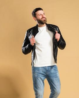 Junger hübscher kerl in einem weißen t-shirt und einer schwarzen jacke auf einem pastellorange.