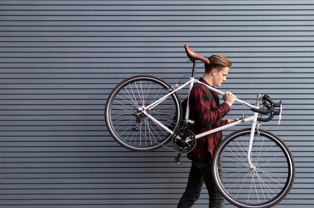 Junger hübscher kerl trägt ein defektes fahrrad auf seinen schultern gegen die wand