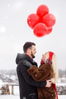 Junger hübscher kerl und mädchen mit luftballons, die am valentinstag gehen