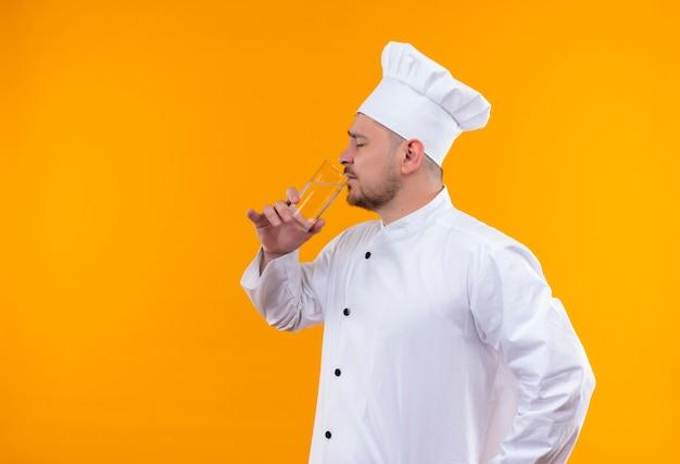 Junger hübscher koch im einheitlichen trinkwasser des küchenchefs mit geschlossenen augen lokalisiert auf orange raum