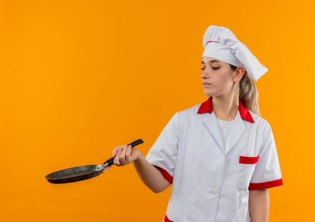 Junger hübscher koch in der kochuniform, die bratpfanne hält und betrachtet