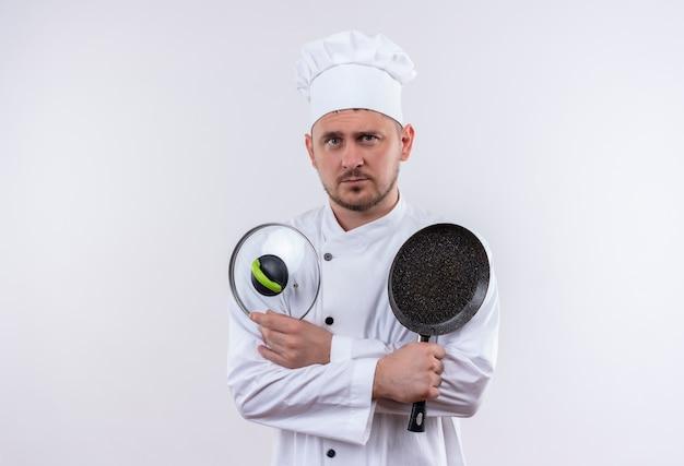 Junger hübscher koch in der kochuniform, die bratpfanne und pfannendeckel hält, die lokal auf weißem raum suchen