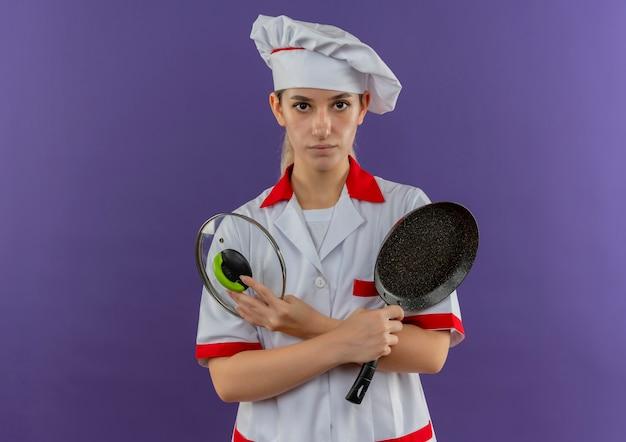 Junger hübscher koch in der kochuniform, die bratpfanne und pfannendeckel sucht