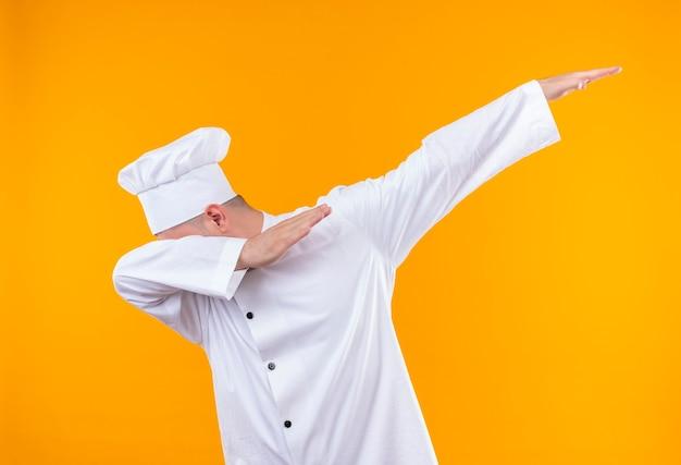 Junger hübscher koch in der kochuniform, die kopf auf arm setzt und einen anderen arm erhöht, der auf orange raum lokalisiert wird