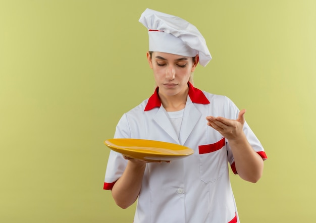 Junger hübscher koch in der kochuniform, die leere platte hält hand hält