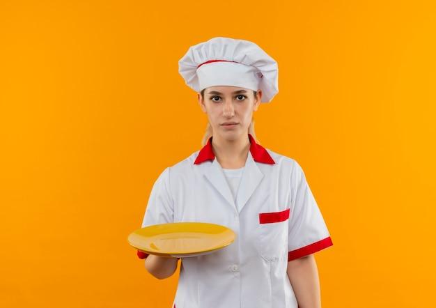 Junger hübscher koch in der kochuniform, die leeren teller sucht