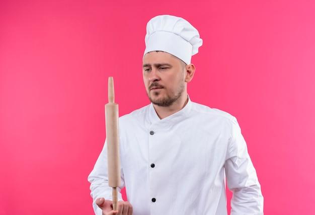 Junger hübscher koch in der kochuniform, die nudelholz hält, das auf rosa raum lokalisiert betrachtet