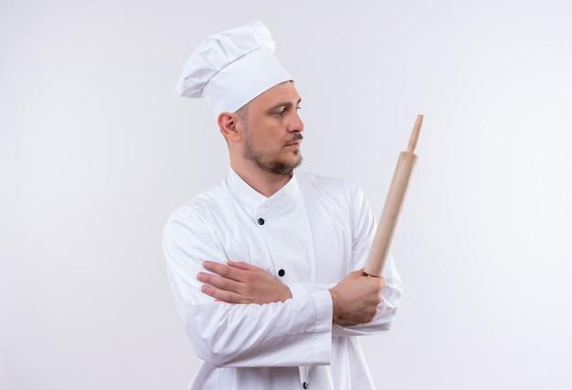 Junger hübscher koch in der kochuniform, die nudelholz hält, das seite lokalisiert auf weißem raum betrachtet