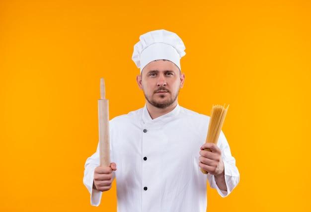 Junger hübscher koch in der kochuniform, die nudelholz und spaghetti-nudeln hält, die auf orange raum lokalisiert suchen