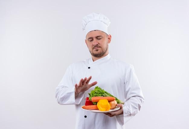 Junger hübscher koch in der kochuniform, die platte mit gemüse hält, das sie betrachtet und hand über ihnen auf lokalisiertem weißen raum hält