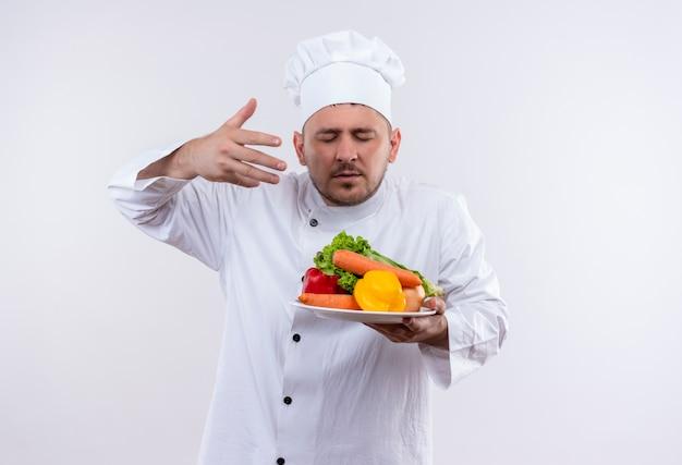 Junger hübscher koch in der kochuniform, die platte mit gemüse hält, das sie mit erhabener hand und geschlossenen augen auf isoliertem weißem raum schnüffelt