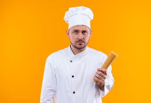 Junger hübscher koch in der kochuniform, die spaghetti-nudeln hält, die auf orange raum lokalisiert suchen