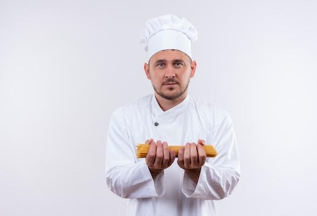 Junger hübscher koch in der kochuniform, die spaghetti-nudeln hält, die lokal auf weißem raum suchen