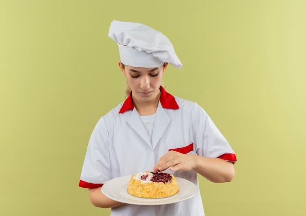 Junger hübscher koch in der kochuniform, die teller des kuchens hält und kuchen lokalisiert auf grünem hintergrund betrachtet