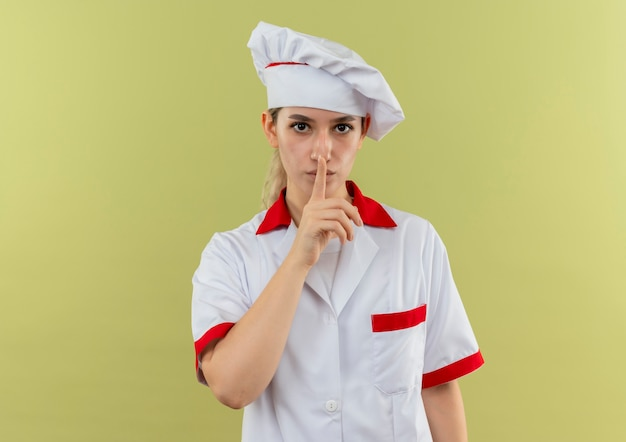 Junger hübscher koch in der kochuniform gestikuliert stille, die lokal auf grünem hintergrund schaut