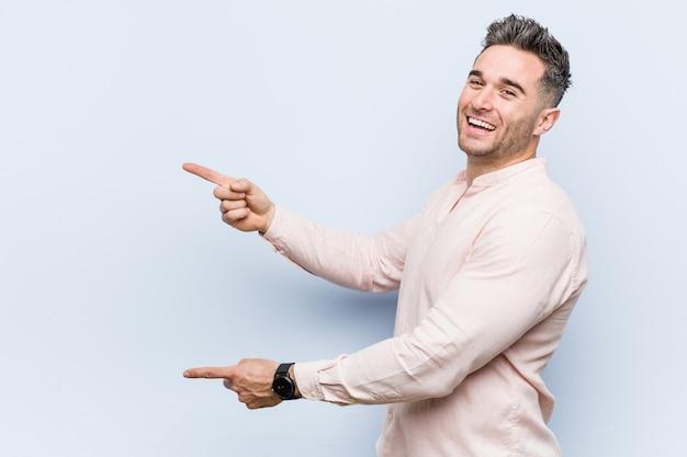 Junger hübscher kühler mann aufgeregt, zeigend mit den zeigefingern weg.