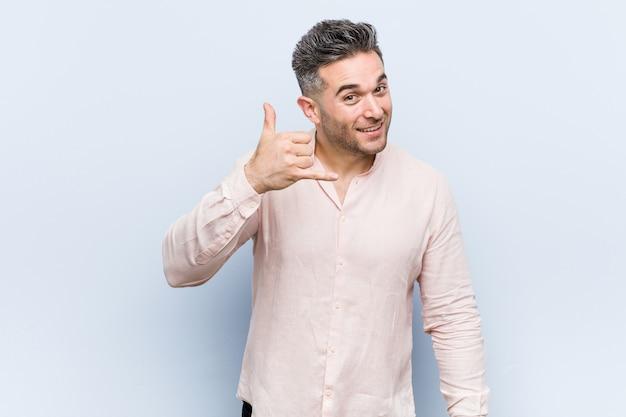Junger hübscher kühler mann, der eine handy-anrufgeste mit den fingern zeigt.