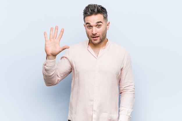 Junger hübscher kühler mann, der fröhlich lächelt und nummer fünf mit den fingern zeigt.