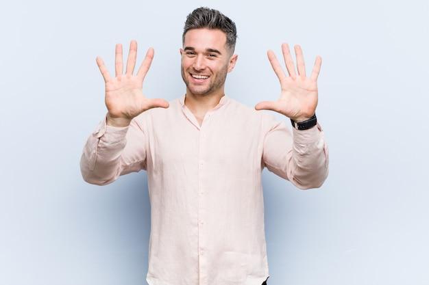 Junger hübscher kühler mann, der nr. zehn mit den händen zeigt.
