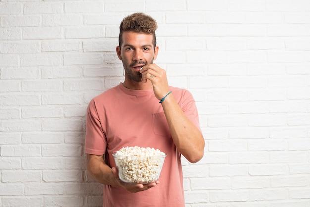 Junger hübscher kühler mann mit popcorns. film- oder filmkonzept