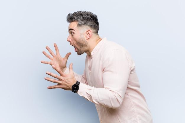 Junger hübscher kühler mann schreit laut, hält augen geöffnet und hände angespannt.