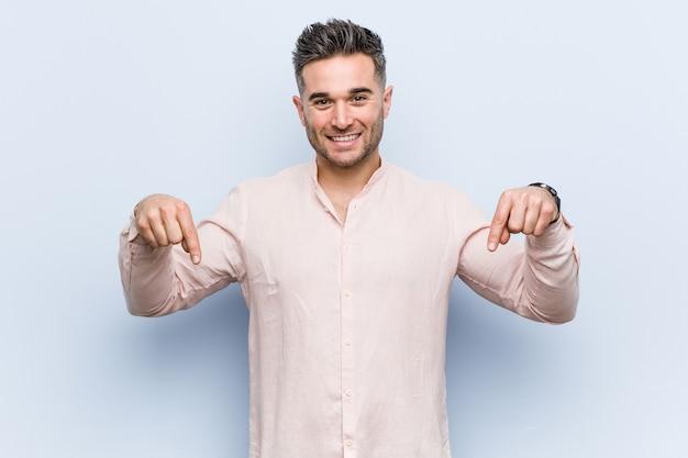 Junger hübscher kühler mann zeigt mit den fingern nach unten, positives gefühl.