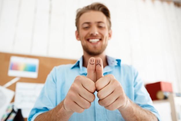 Junger hübscher lächelnder geschäftsmann, der daumen oben mit lustigen gesichtszeichnungen zeigt. hände im fokus. weiße moderne büroeinrichtung
