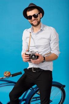Junger hübscher lächelnder glücklicher mann, der auf hipster-fahrrad reist, weinlesekamera auf blauem studiohintergrund haltend, hemd, hut und sonnenbrille tragend, fotograf, der fotos macht