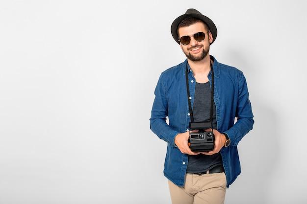 Junger hübscher lächelnder glücklicher mann, der weinlesefotokamera lokalisiert auf weißem studiohintergrund hält, jeanshemd, hut und sonnenbrille tragend, fotograf reist und fotografiert
