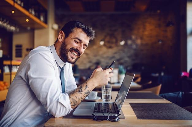 Junger hübscher lächelnder kaukasischer tätowierter eleganter geschäftsmann in hemd und krawatte unter verwendung des smartphones während des sitzens im café. auf dem tisch steht ein laptop.