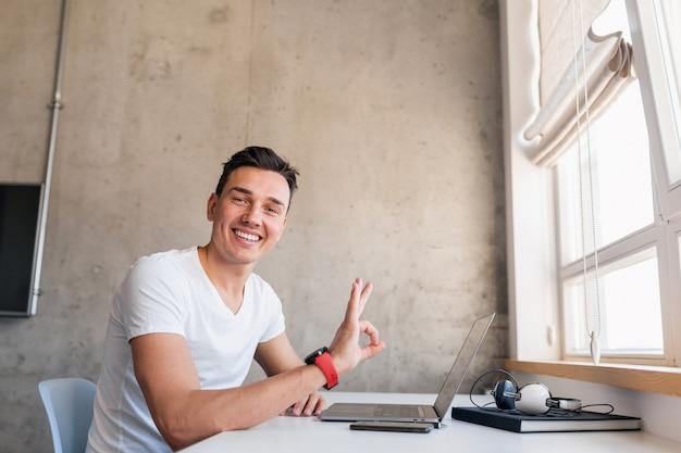 Junger hübscher lächelnder mann im lässigen outfit, das am tisch sitzt und am laptop arbeitet, freiberufler zu hause