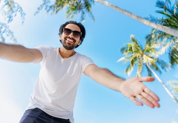 Junger hübscher lateinamerikanischer mann in einem weißen t-shirt und einer sonnenbrille auf blauem himmel und palmen, streckt seine hand zur linse aus, bild von unten