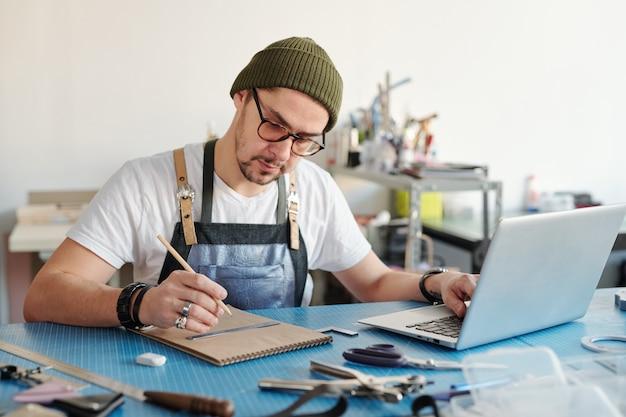 Junger hübscher lederarbeiter in der schürze und im mützenhut, die skizze im notizblock machen, während sie vor laptop in der werkstatt sitzen