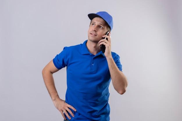 Junger hübscher lieferbote in der blauen uniform und in der kappe, die auf handy mit nachdenklichem ausdruck auf gesicht steht, das über weißer wand steht