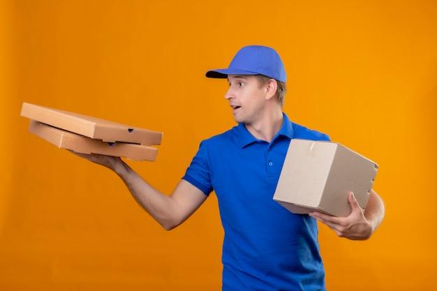 Junger hübscher lieferbote in der blauen uniform und in der kappe, die box-paket und pizzaschachteln hält, die beiseite schauen überrascht über orange wand stehen