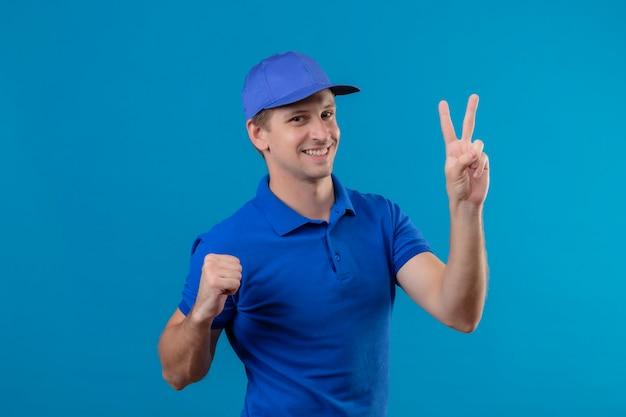 Junger hübscher lieferbote in der blauen uniform und in der kappe, die das lächeln der nummer zwei zeigt, das fröhlich über der blauen wand steht