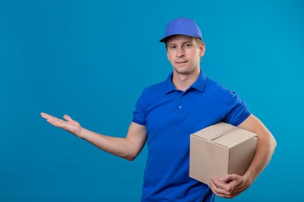 Junger hübscher lieferbote in der blauen uniform und in der kappe, die kastenpaket darstellt, präsentiert mit arm seiner hand kopiert raum, der über blauer wand steht