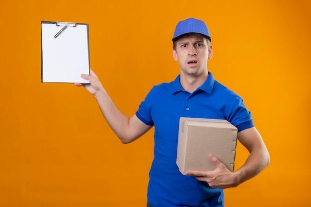 Junger hübscher lieferbote in der blauen uniform und in der kappe, die kastenpaket und zwischenablage hält, die erstaunt und überrascht stehen, über orange wand stehen
