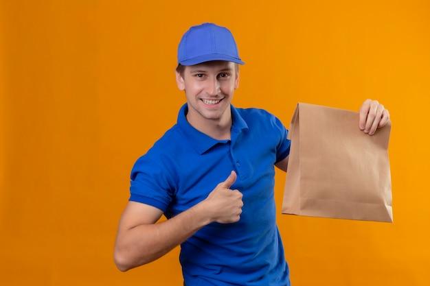 Junger hübscher lieferbote in der blauen uniform und in der kappe, die papierpackungen halten, die zuversichtlich schauen