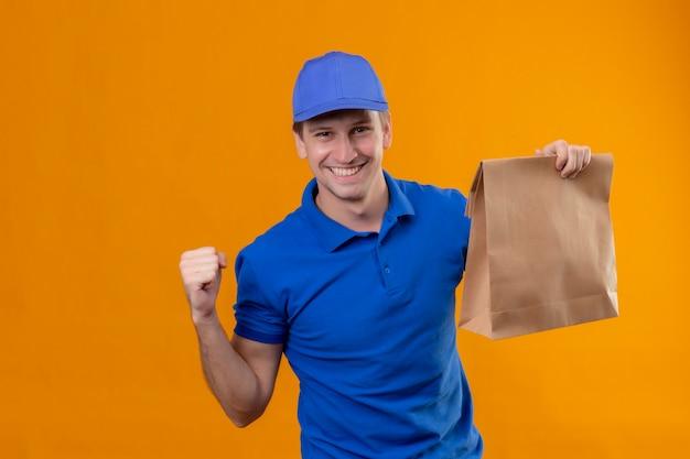 Junger hübscher lieferbote in der blauen uniform und in der kappe, die pizzaschachteln hält, die faust glücklich und zufrieden heben, die sein erfolgssiegerkonzept freuen, das über orange wand steht