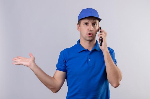 Junger hübscher lieferbote in der blauen uniform und in der kappe, die verwirrt sprechen, die auf handy sprechen