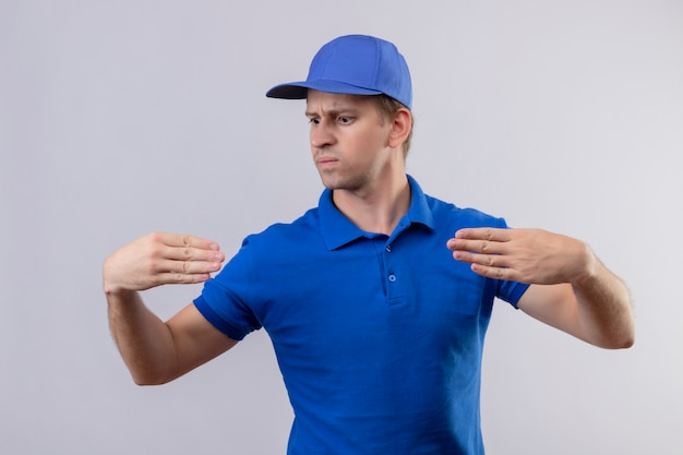 Junger hübscher lieferbote in der blauen uniform und in der kappe gestikuliert mit handkörpersprachenkonzept, das über weißer wand steht