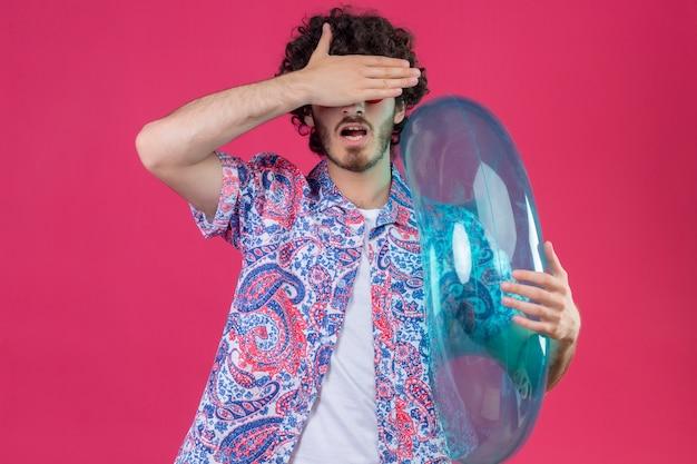 Junger hübscher lockiger mann, der schwimmring hält, der augen mit hand auf isolierter rosa wand schließt