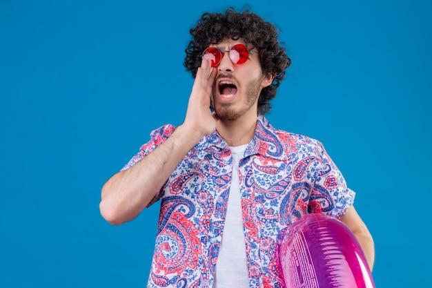 Junger hübscher lockiger mann, der sonnenbrillen hält, die schwimmring halten, der jemanden mit hand nahe mund auf isolierter blauer wand anschreit